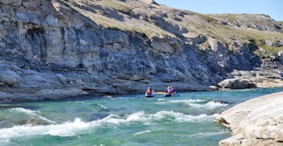 Trois personnes dans une embarcation, pagayant dans les rapides d'une rivière, près d'une paroi rocheuse.