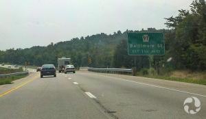 Des automobiles roulant sur une autoroute, avec une pancante routière en bordure de la route.