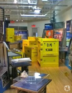 Des caisses et des panneaux d'exposition entreposés dans une salle.