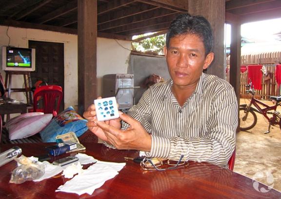 Un homme montre une plaquette comportant 11 zircons bleus de différentes tailles.