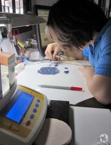 Une femme triant des saphirs dans un laboratoire.