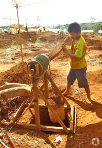 Un homme remonte un seau de terre d'un trou à l'aide d'un treuil manuel.