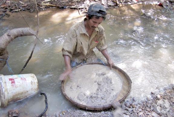 Assis dans un petit cours d'eau, un homme nettoie de la terre boueuse dans un tamis.