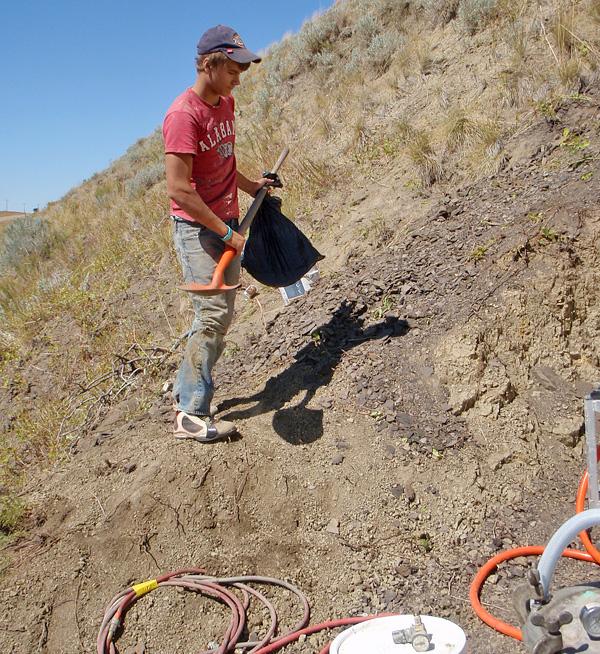 Un homme debout sur le flanc d'une colline tenant une pelle.