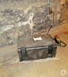 Une boîte noire sur le sol branchée à une prise murale dans un corridor.