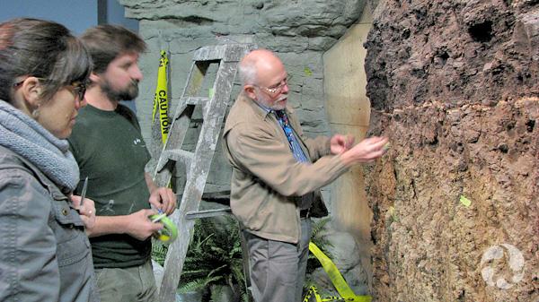 Trois personnes debout près du mur de la galerie en construction.