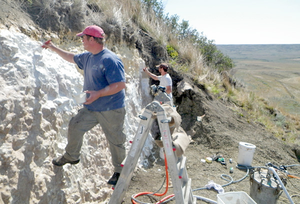 Deux hommes appliquent le matériel de moulage sur la paroi de roche sédimentaire.