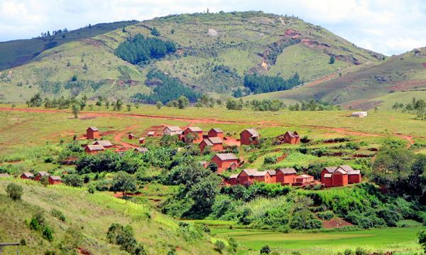 Un village composé de maisons en brique rouge, dans une vallée entourée de collines.