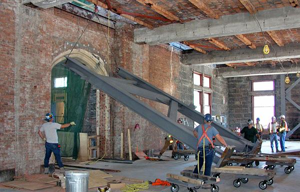 Installation d'une structure d'acier portante dans une galerie en rénovation.