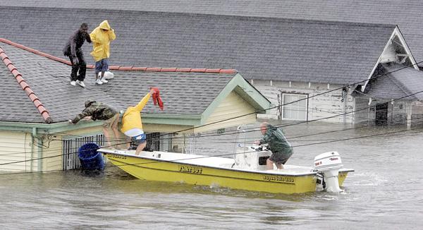 Un bateau à moteur avec trois personnes à son bord près du toit d'une maison où se trouvent deux rescapés.