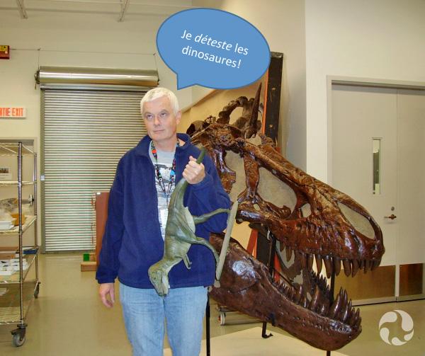 Le gestionnaire des collections de fossiles, Kieran Shepherd, lève les yeux au ciel alors qu'il tient un modèle de dinosaure par la queue.