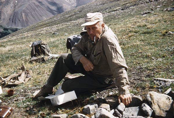 Alf Erling Porsild assis sur l'herbe, dans un paysage montagneux.