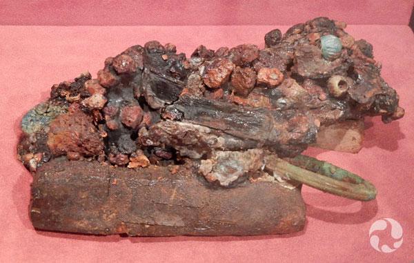Un artefact composé de matériaux et d'objets agglomérés notamment des perles, des anneaux, des pièces de bronze, un ciseau et des morceaux de bois.