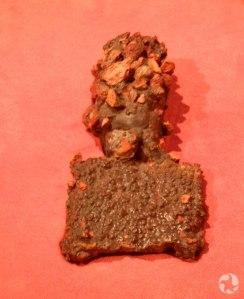 Un outil de jardinage antique couvert de lave et de roches.
