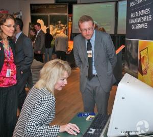 Une femme assise utilise l'ordinateur du kiosque présentant la Base de données canadienne sur les catastrophes, dans l'exposition La nature déchaînée.