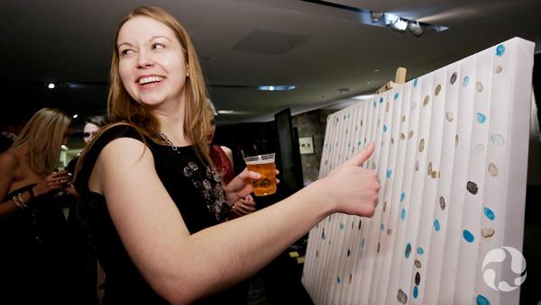 Une femme souriante imprime son empreinte digitale sur une toile.