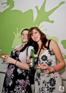 Un verre à la main, deux jeunes femmes souriantes posent devant une murale où l'on voit des grenouilles stylisées.