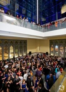 Une foule de personnes dansent dans la mezzanine du Musée, pendant que d'autres les regardent d'un étage supérieur.