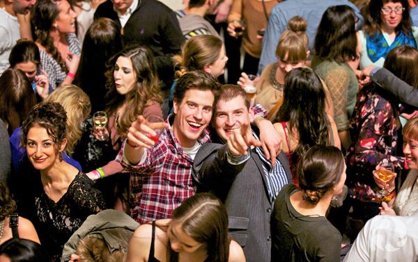Deux jeunes hommes dans une foule sur un plancher de danse sourient au photographe.