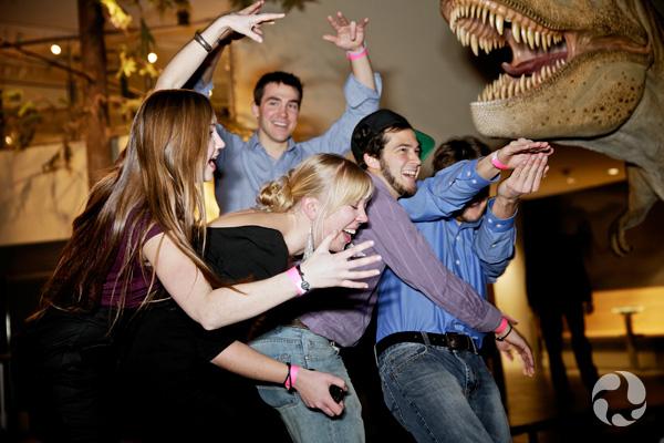 De jeunes adultes prennent des poses pour imiter des dinosaures dans une galerie du Musée.