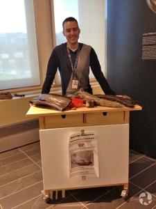 Jordan Mallon debout derrière le comptoir d'un kiosque, dans la Galerie des fossiles Talisman Energy.