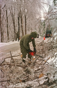 Un soldat utilise une scie à chaîne pour couper un arbre qui est tombé sous le poids du verglas.