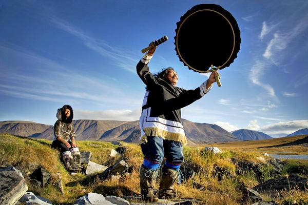Une personne frappe un large tambourin avec un bâton, dans la toundra en été. Une seconde personne, assise sur une roche, la regarde.
