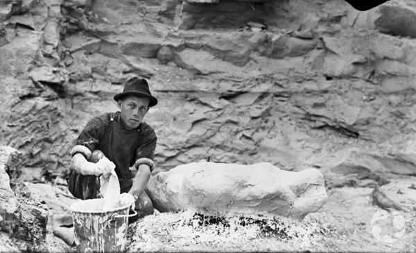 Un homme accroupi devant une falaise rocheuse trempe un linge dans un seau contenant du plâtre, près d'une coque en plâtre.