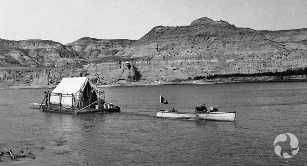Un petit bateau remorquant un radeau avec une tente dessus.