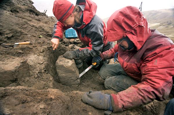 Deux femmes travaillent dans une cavité creusée sur une pente dénudée.