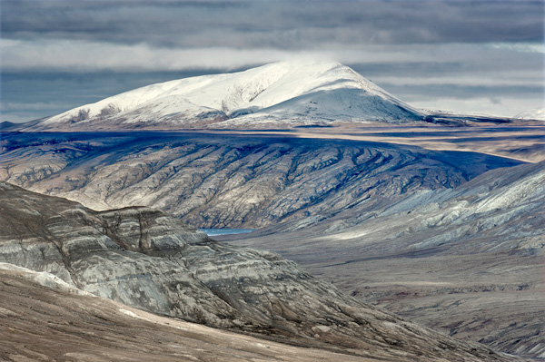 Un paysage rocailleux avec une vue plongeante sur le fjord à partir de la plaine et une colline couverte de neige dans le lointain.