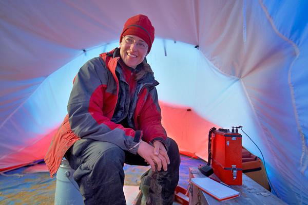 Natalia Rybczynski assise dans une tente avec une radio satellite à ses côtés.