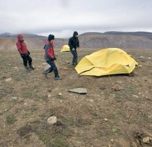 Trois personnes approchant une tente effondrée par le vent dans un paysage rocailleux.