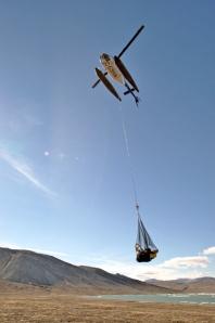 Un petit hélicoptère avec un filet de marchandises suspendu.