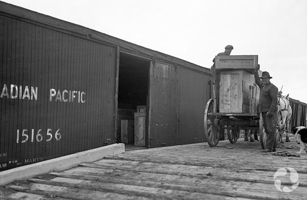 Photo d'archives: une charrette attelée à un cheval et contenant de grandes caisses de bois est arrêtée près d'un wagon de train, dans une gare. Deux hommes se tiennent près de la charrette.