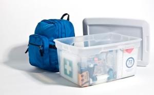 Un sac à dos et une boîte de plastique transparent contenant des articles d'urgence.
