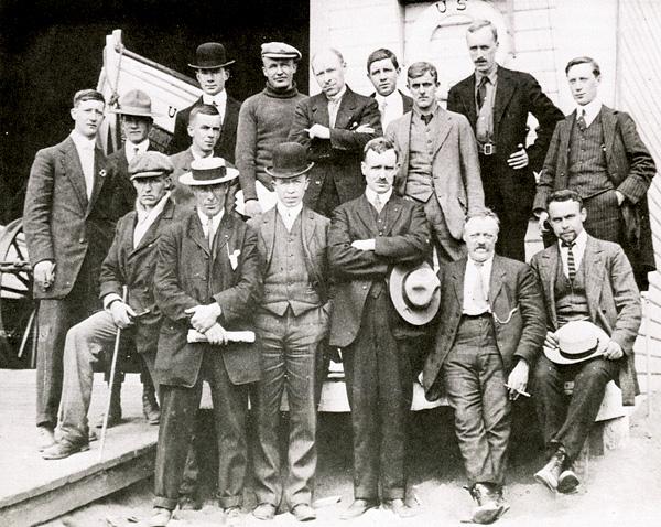 Seize hommes en complet posent pour une photo de groupe.