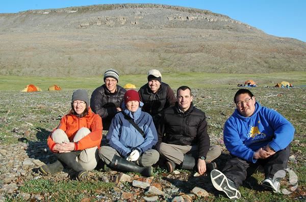Un groupe de six personnes assises posent pour une photo. On aperçoit une tente et des collines à l'arrière-plan.