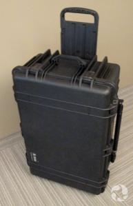 Une valise en plastique, avec roulettes et poignée.