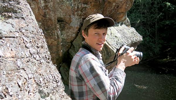 Roger Bull debout devant une paroi rocheuse, tenant un appareil photo à la main.