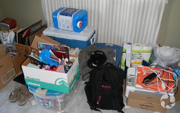 Boîtes et équipement de camping étalés au sol.