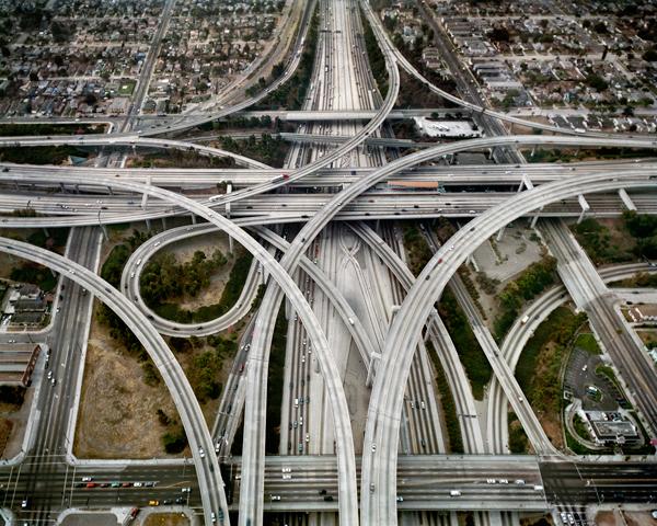 Photographie aérienne montrant plusieurs autoroutes et routes qui s'entrecroisent dans un milieu urbain.
