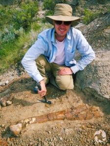 Jordan Mallon accroupi derrière un os incrusté dans le sol.