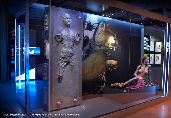 Un modèle de Han Solo en carbonite à côté d'un modèle de la princesse Léia et d'une photo de Jabba le Hut.