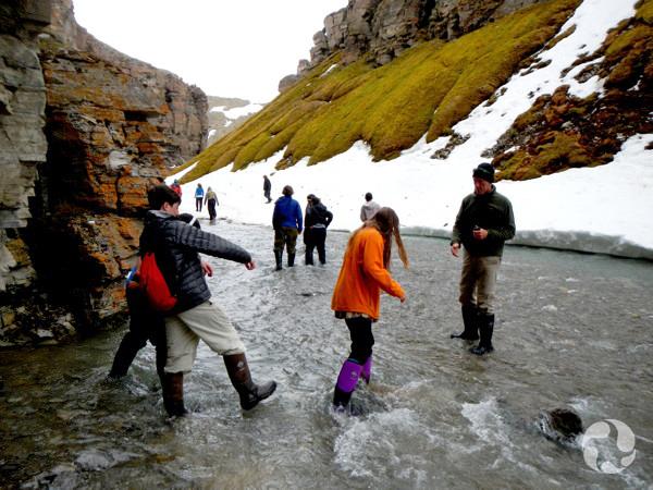 Un groupe traverse un ruisseau dans un canyon.