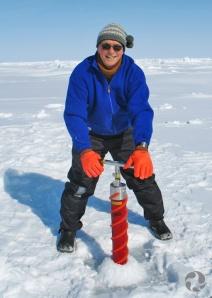 Un homme debout dans la neige avec à la main un instrument servant à prélever une carotte de glace.