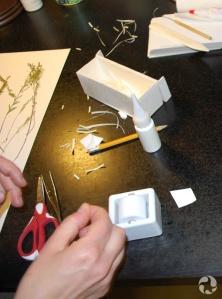 Une main de femme sur la table parmi des outils servant au montage de plantes.