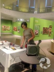 Une femme manipule des objets sur une table, près d'un projecteur, dans une salle d'exposition.