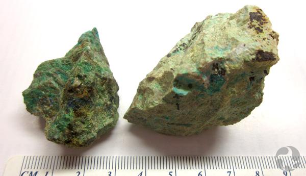 Des spécimens de mrazekite et hechtsbergite sur une table, à côté d'une règle indiquant leur taille.