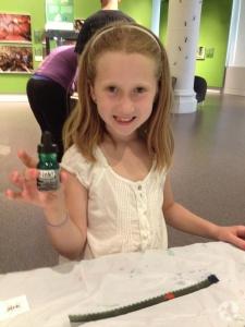 Une fillette montre le pot d'encre qu'elle tient dans sa main.
